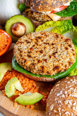 Photo pour Tasty vegetarian healthy green food, homemade burgers made from orange lentils legumes with green lettuce and fresh ripe avocado - image libre de droit