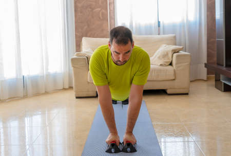 Photo for Bearded man in low shape exercising with black and green sportswear in his living room in front of the sofas on a mat - Royalty Free Image