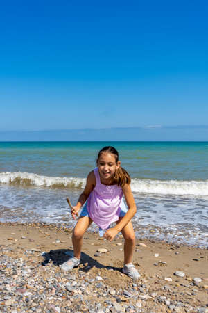 Foto de Little girl dressed in pastel colors jumping and playing on the stone and sandy shore of the Mediterranean Sea. Fun concept - Imagen libre de derechos