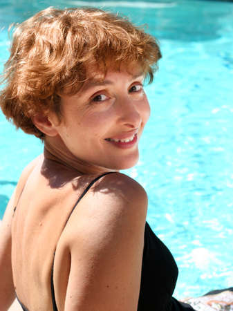 Pretty mature woman smiling by the pool