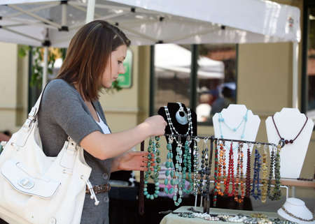 A teenage girl looking at gemstone necklaces at the market