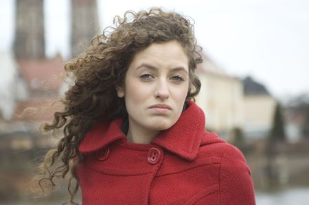 Teenage girl in Poland, portrait. Young girl with curly hairs wearing red coat, posing in Wroclaw city.