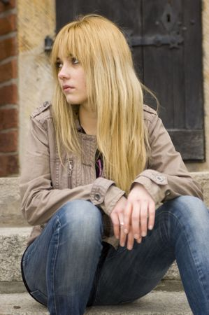Young, pretty and kind teenage girl in Poland. Schoolgirl with casual clothes, blonde hairs. Peaceful and calm face expression.