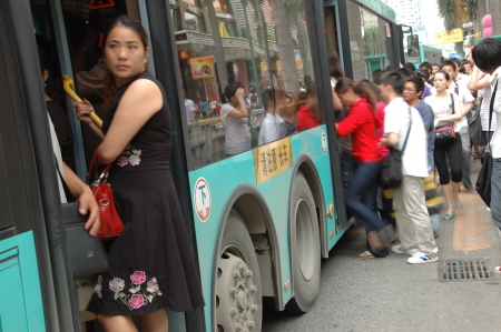 CHINA, SHENZHEN - AUGUST 20: overpopulated city in Guangdong province. Crowd of people in city center waits in queue and pushes to the buses after work on August 20, 2010.