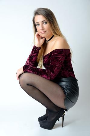 Foto de Beautiful Polish model. Well-built girl with maroon top, black shorts, high heels and stockings. - Imagen libre de derechos