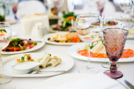Photo pour Served for banquet restaurant table with dishes, snack, cutlery, wine and water glasses. - image libre de droit