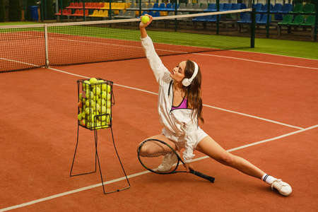 Photo for The girl in a sports uniform sits on a tennis court - Royalty Free Image