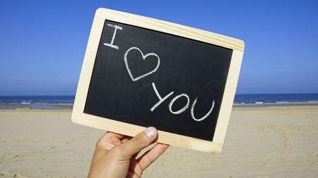 I love you written on a chalkboard on the beach