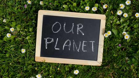 Our planet written on a chalkoard in a park