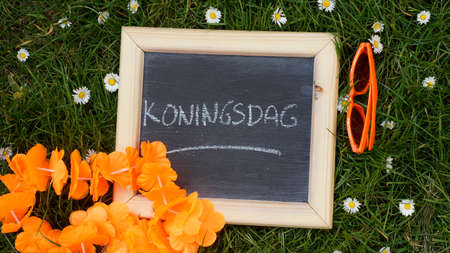 Kingsday in Dutch written on a chalkboard in a park