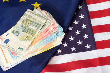 Flags of the EU and USA and many Euro banknotes