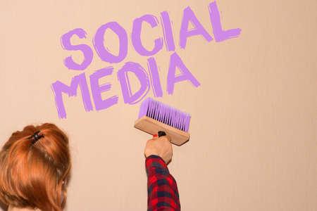 A woman paints on the wall slogan social media