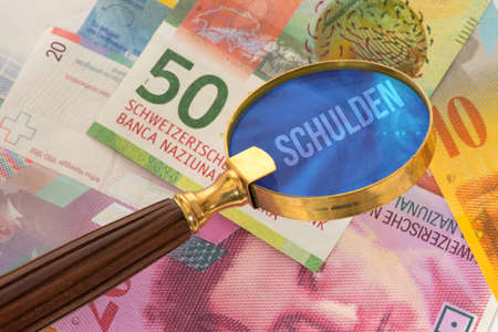 Banknotes Swiss francs, a magnifying glass and the debts