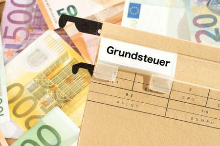 Photo pour Euro banknotes and a folder with the imprint property tax - image libre de droit