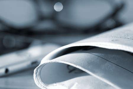 Photo pour A newspaper, reading glasses and a smartphone - image libre de droit