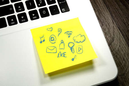 A computer and a note with different icons for social media and other services on the Internet