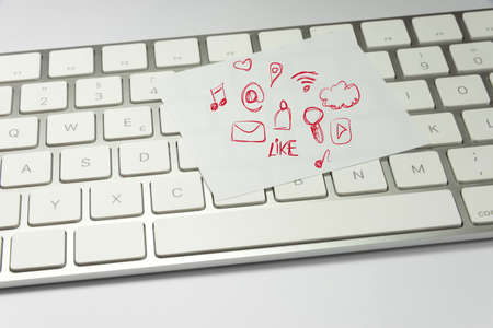A computer and a note with various icons for social media and other services on the Internet
