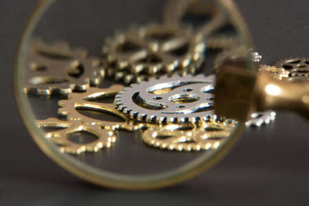 A magnifying glass and different gears