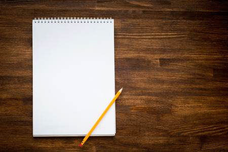 notebook with pencile on a wooden background
