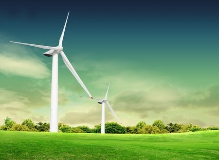 Wind turbine on the green grass over the blue clouded sky