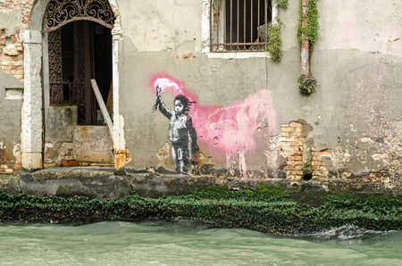 VENICE, ITALY - MAY 15, 2019:  Stencil street art of a child wearing a lifejacket and waving a flare attributed to graffiti artist Banksy.  Viewed from a public street overlooking the Rio di Ca'Foscari in the Dorsoduro student district of Venice.