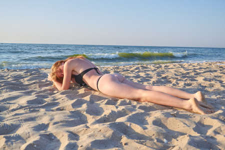 Photo for Positive and serene young woman sunbathing at seaside with closed eyes. - Royalty Free Image