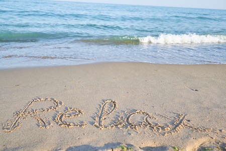 Photo for relax word is written on the beach sand with water - Royalty Free Image