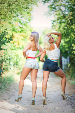 Foto de Modern youth female fashion trends, two girls in outfits with visible thongs - Imagen libre de derechos