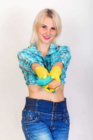Photo pour Happy smiling blonde woman housekeeper wearing yellow rubber gloves looking at camera and shows sponges for washing - image libre de droit