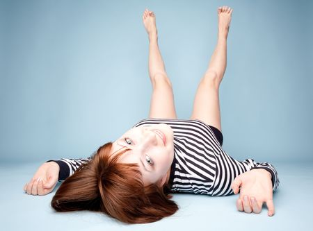 Smiling girl lying upside down on blue background