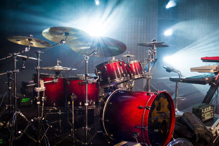 drum set on stage and light background; empty stage with instruments ready for performance