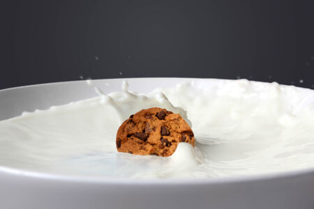 Cookie falling into milk
