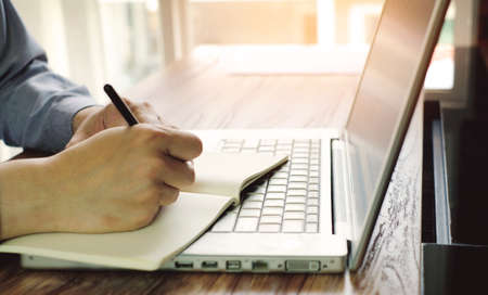 a man is writing some word on notebook with laptop in office room
