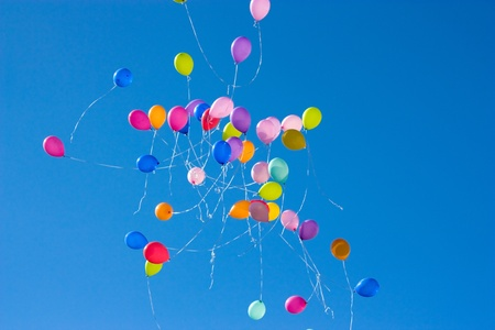 Balloons released into the clear blue sky after a wedding with closeup of a small group of balloons