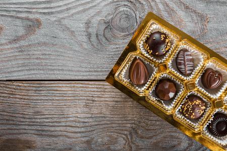 Photo pour Assorted chocolate candies on a wooden background - image libre de droit