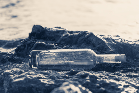 Photo pour Message in a corked bottle on the shore, hope of salvation - image libre de droit