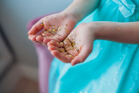 Photo for Little girls hands covered with gold glittering stars - Royalty Free Image