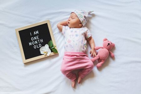 Photo pour One month old baby girl wearing floral bodysuit and pink pants and laying down on white background. Shot from overhead. - image libre de droit