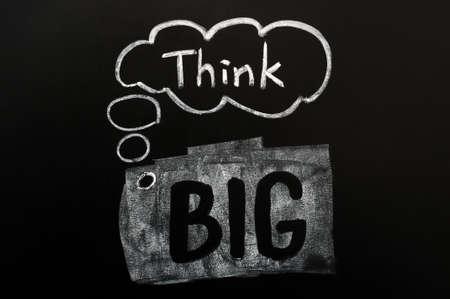 Think big handwritten in chalk on a blackboard