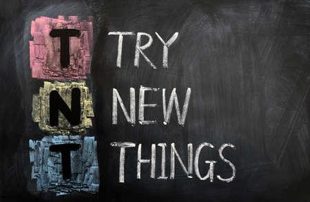 Acronym of TNT for Try New Things written in chalk on a blackboard