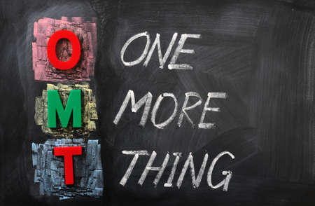 Acronym of OMT for One More Thing written in chalk on a blackboard