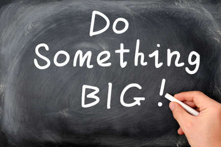 Do something big written with chalk on a blackboard background, with a hand holding chalk