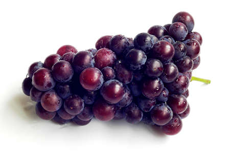 A cluster of ripe purple grapes on a white background