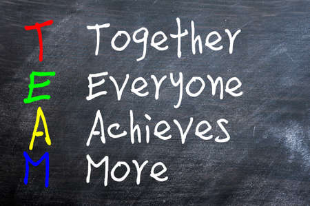 TEAM acronym for Together Everyone Achieves More written on a smudged blackboard