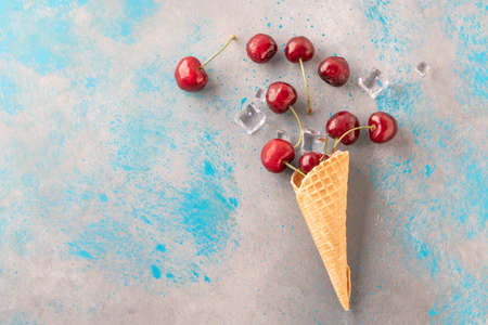 Foto de ripe and fresh cherry fruits and ice cubes coming out from ice cream cone - Imagen libre de derechos