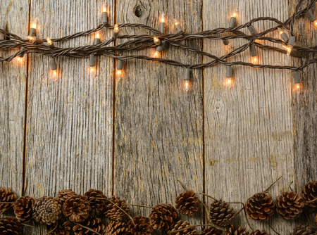Photo for Christmas Lights and Pine cones on Rustic Wood Background - Royalty Free Image
