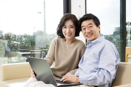 Photo pour Middleaged Asian Couple Looking at a Laptop in Livingroom - image libre de droit