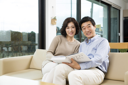 Photo pour Middleaged Asian Couple Smiling in the Living room - image libre de droit