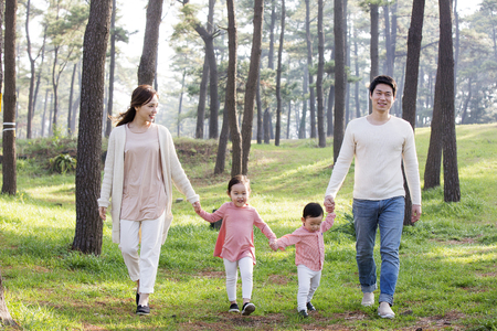 Happy Asian Family Holding Hands and Walking in Forest