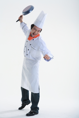 A male cook swinging a frying pan